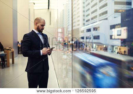 Young man owner of successful enterprise is typing on mobile phone text message to his partner that he wait in restaurant while is standing near window with view of a big metropolitan city in action