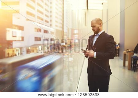 Bearded man skilled managing director is searching on web site via mobile phone needed information for meeting with clients while is standing near window with view of the main street of Hong Kong