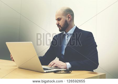 Young serious man investor is examining on laptop computer activity of company which he wants to invest. Male skilled employer is reading on portable net-book resume before interview with specialists