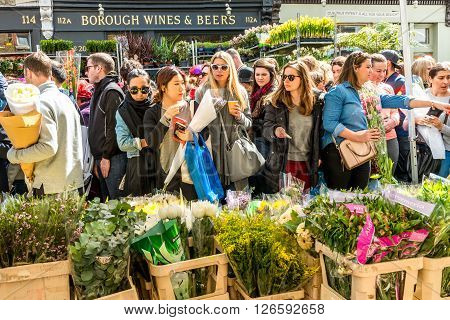 London United Kingdom - April 17 2016: Columbia Road Flower Sunday market. Street traders are selling their stock people choosing flowers