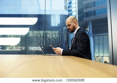 Man proud CEO is developing recommendations for improving the planned activities by using mobile phone and net-book. Male manager is watching video on cell telephone during work on portable net-book