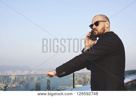 Young man skilled managing director having cell telephone conversation with financial manager during his business trip in New York while is standing on building roof against city view with copy space