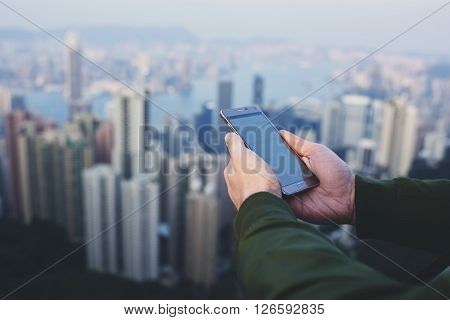Closeup of hipster guy is checking e-mail on smart phone while is standing on last skyscraper floor with view of Hong kong cityscape on cold foggy day. Young male connecting to internet via cellphone