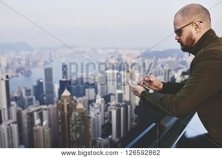 Bearded businessman is checking e-mail in network via mobile phone while is standing on a building roof against blurred business district in New York Background with copy space for your advertising