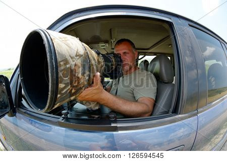 wildlife photographer sitting in the car