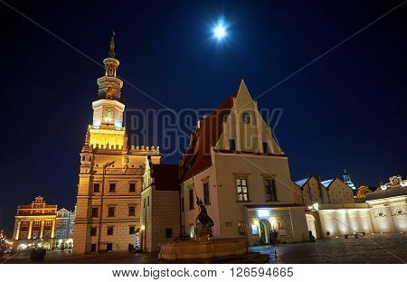 Old Market with city hall and moon in Poznan by night