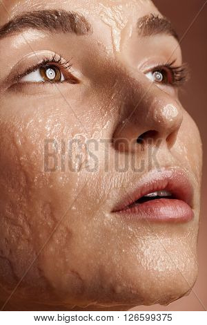 Beautiful woman with good skin with face in water in close up photo on brown background. Healthy and spa