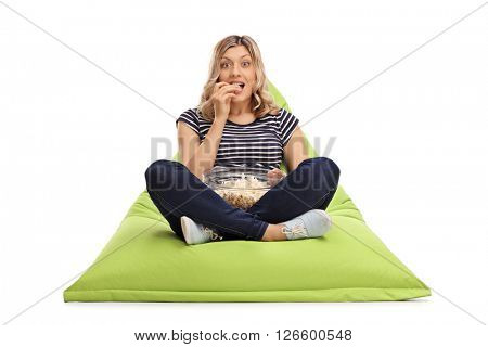 Excited woman eating popcorn seated on a green beanbag and looking at the camera isolated on white background