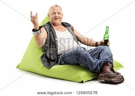 Mature punk rocker drinking beer seated on a beanbag and making a rock hand gesture isolated on white background