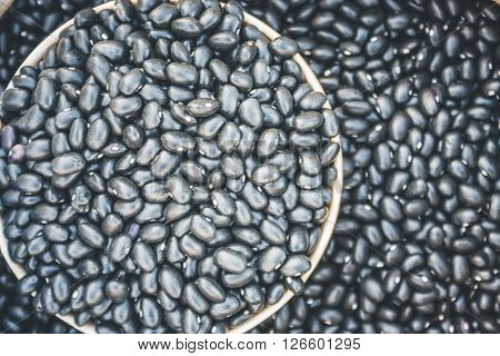 Close-Up View Of Black Beans Scattered Beans Around On A Cup With Beans Background. (View From Above) ** Note: Visible grain at 100%, best at smaller sizes