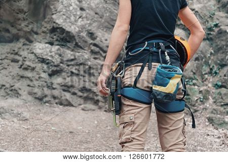 Unrecognizable woman rock climber wearing in safety harness with climbing equipment and helmet outdoor