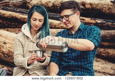 Traveler loving couple resting outdoor. Young man pouring tea from thermos to cup of young woman
