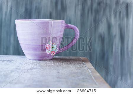 pink cup with teabag on a table