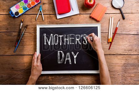 Mothers day composition. Hands of unrecognizable man writing with chalk on little board, school supplies. Studio shot on wooden background.