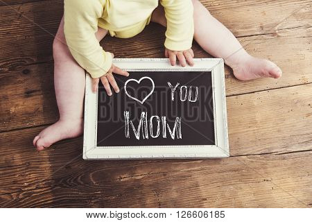 Mothers day composition. Unrecognizable baby in yellow onesie holding a chalk sign in picture frame. Studio shot on wooden background.