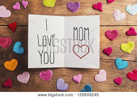Mothers day greeting card. Mothers day composition. Colorful fabric hearts. Studio shot on wooden background.