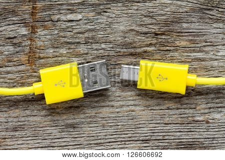 Yellow USB cable on wooden tableclose-up view