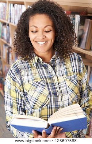 Attractive Young Female Student Reading Book In Library