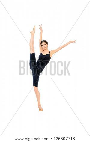 Beautiful graceful ballet dancer in black ballet leotard posing at studio. Jump, movement. Art concept. Isolated over white.