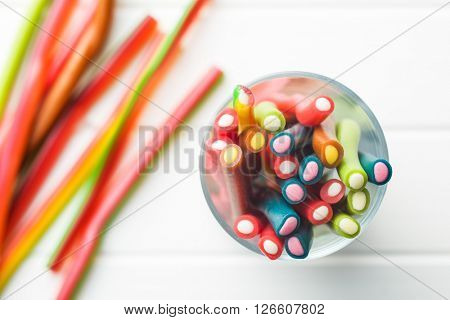 Sweet gummy sticks with different flavor. Top view of tasty candy in glass cup.