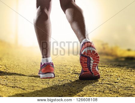close up feet with running shoes and female strong athletic legs of sport woman jogging in fitness training workout on off road trail track design in advertising poster style sunset extreme
