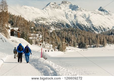 ST MORITZ SWITZERLAND - FEBRUARY 08 2016: People walking along side the St Moritzersee in the Emgadin valley Switzerland in winter.