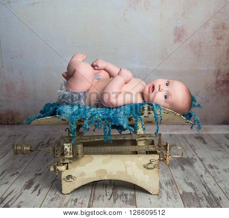 cute little baby with legs up lying on child scales on wooden floor