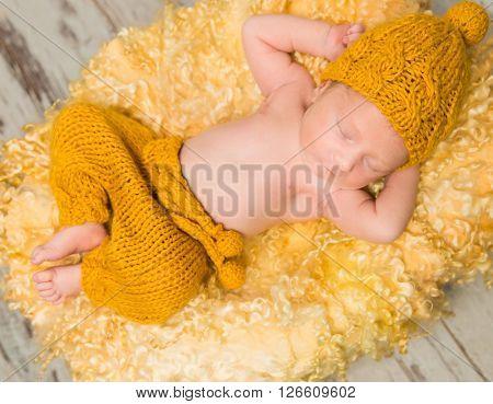 beautiful newborn baby lying on woolen blanket in wicker basket