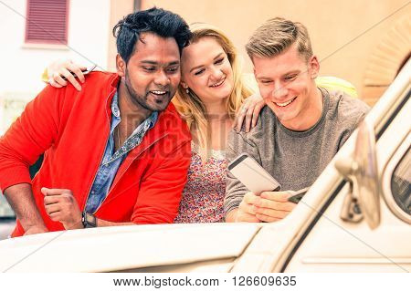 Multiracial young friends watching mobile phone on car bonnet - Cheerful guys leaning on vintage auto using smartphone technology - Concept of multicultural friendship and joyful moment on a road trip