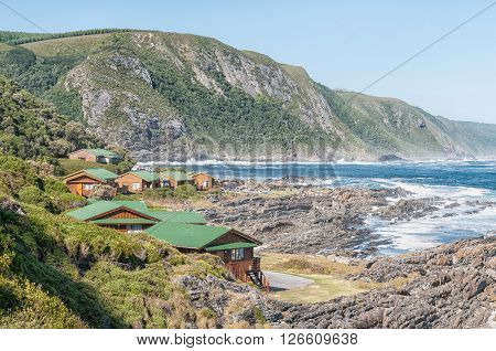 STORMS RIVER MOUTH SOUTH AFRICA - FEBRUARY 28 2016: The restaurant chalets and the day visitor picnic site at Storms River Mouth. A viewpoint is visible on top of the mountain
