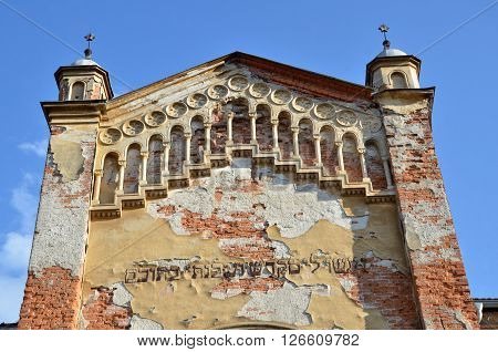 Bytca Slovakia - April 13 2016: Detailed view at the top of desolate jewish synagogue with some type. Front view blue sky in background.