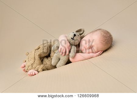 sweet sleeping newborn baby embracing toy-hare on blanket