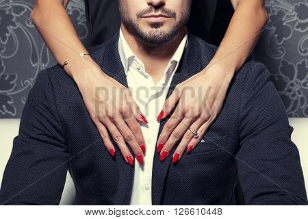 Sexy woman hands with red nails embrace rich man
