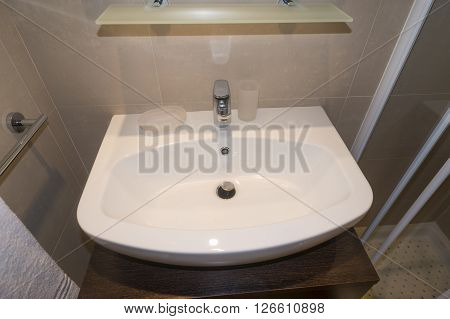 white clean ceramic washbasin with metallic tap in home bathroom