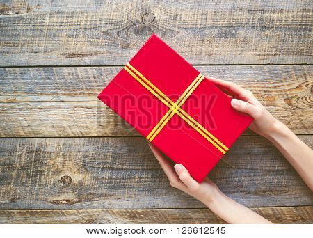 red gift box in girl hands  on old brown wooden table