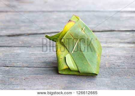 the Thai dessert with banana leaf on the wooden table