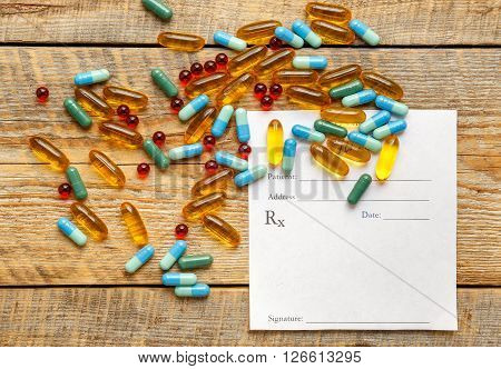 blank medical prescription and pills on wooden table isolated