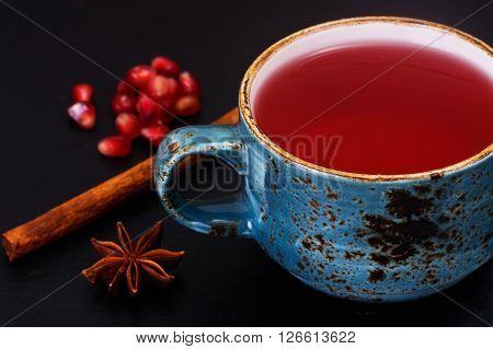 Red Tea with beautiful cup, decorated with cinnamon and pomegranate. Studio Photo