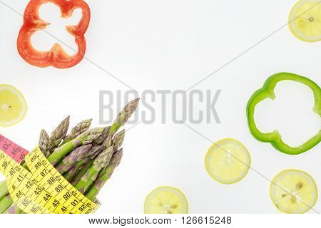 Asparagus Spears With Measuring Tape, Lemon Slices And Pepper Rings, On White Background With Copy-s