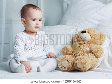 one year old baby in bed at home with a toy