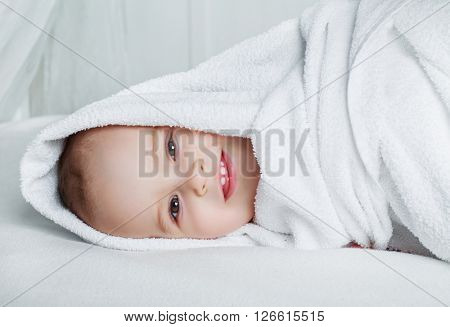 one year old baby with a towel in bed at home