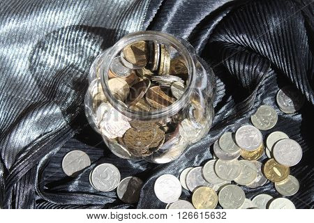 glass bowl with shine coins inside and near money on black day