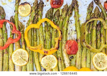 Roasted Asparagus Spears With Lemon Slices, Cherry Tomatoes, Bell Pepper Rings And Seasoning.