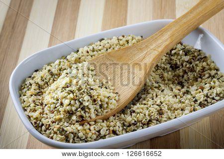 Hemp seeds in wooden spoon in white bowl
