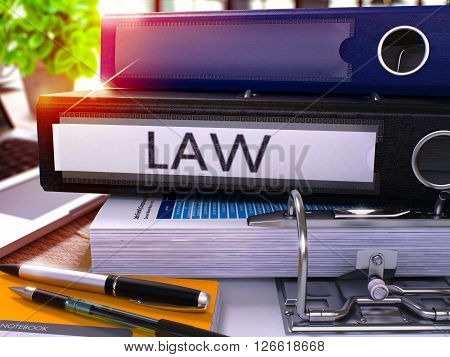 Black Ring Binder with Inscription Law on Background of Working Table with Office Supplies and Laptop. Law - Toned Illustration. Law Business Concept on Blurred Background. 3D Render.