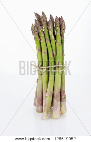 Bunch of asparagus tied with raffia cord isolated on white background.