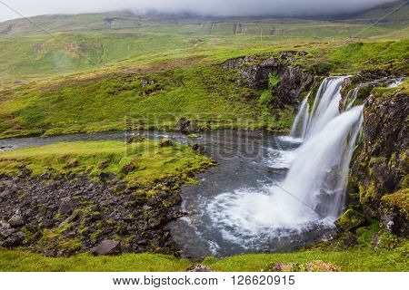 Foggy day in Iceland. Powerful cascading waterfall on the mossy cliff