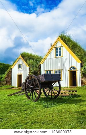 The ancient two-wheeled wooden cart on the front lawn. The village first settlers in Iceland. The recreated village - museum of pioneers - Vikings
