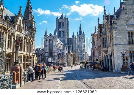 Ghent, Belgium - April 12, 2016: Vibrant color street view of Ghent, Belgium with St Nicholas' Church, beautiful houses and people nearby.