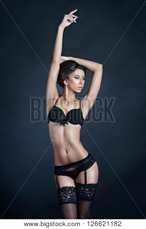 Beautiful sexy lady in elegant panties and bra isolated on a black background. Fashion portrait of model indoors. Beauty brunette woman with attractive body in lace lingerie. Female ass of naked girl